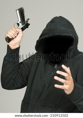 Hooded criminal with gun in hand