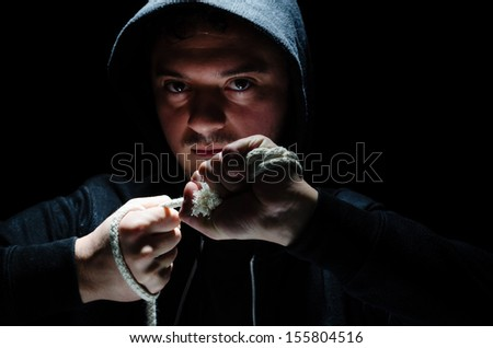 Hooded male with an intimidating expression, against dark background