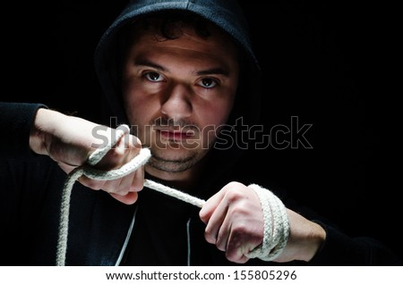 Hooded Male with an intimidating expression, against dark background - stock photo