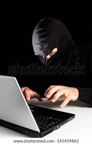 Hooded thief stealing a laptop data