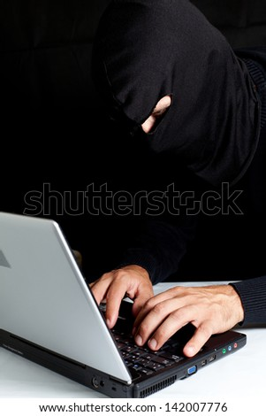 Hooded thief stealing a laptop data - stock photo
