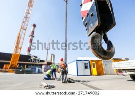Hook of a mobile lifting crane on a construction site, capable of lifting 25 tons of load with workers in the background. Heavy duty machinery for heavy construction industry.  - stock photo
