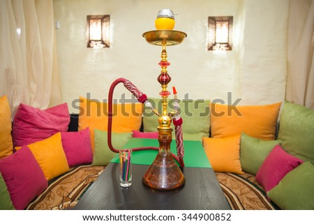 hookah placed on table in the room with Persian carpet and lots of colorful pillows