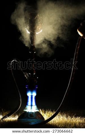 hookah smoke on the street at night - stock photo