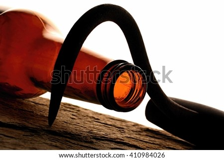 Hooked on alcohol. Beer bottle and hook. - stock photo