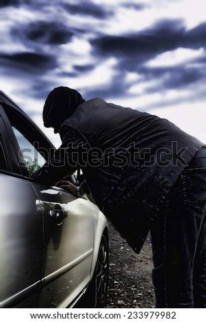 Hooligan breaking into the car - stock photo