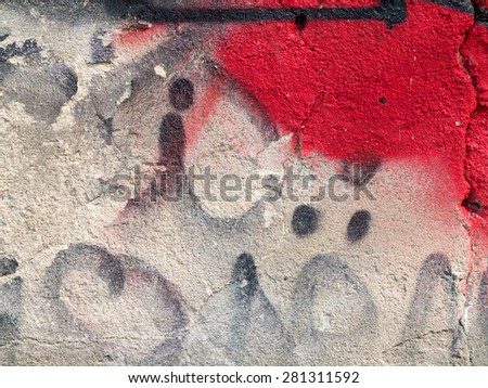 Hooligan smeared paint the walls of the old building. Landscape style. Grungy concrete surface with cracks, scratches and streaks of paint. Great background or texture.