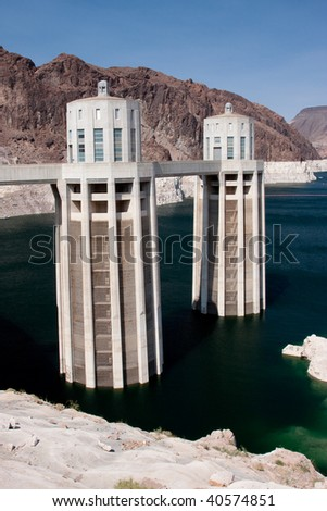 Hoover Dam's sculptured turrets rising seamlessly from the dam face and clock faces on the intake towers set for the time in Nevada and Arizona. - stock photo