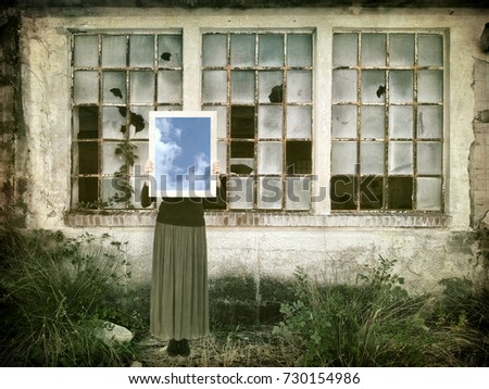 Hope amid desolation. Woman with mirror reflecting blue sky in rundown, abandoned urban setting.