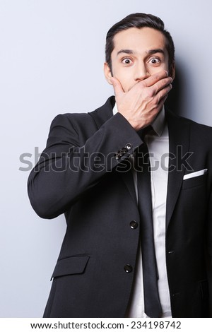 Hope, I do not say too much. Excited young man in formalwear covering mouth with hand and looking at camera while standing against grey background - stock photo