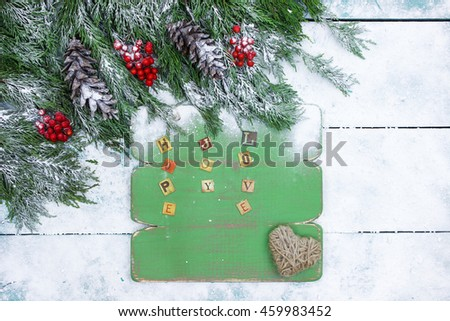 Hope, Joy, Love on green wood sign with Christmas tree garland with pine cones and snow border