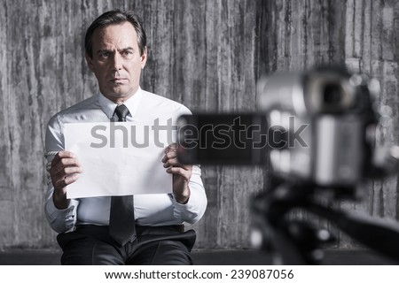 Hopeless hostage. Frustrated businessman caught by a criminal sitting in front of a dirty wall and holding paper while video camera filming it on the foreground - stock photo
