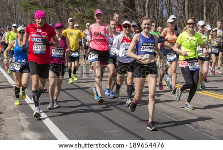 HOPKINTON, USA - APRIL 21: Amateur athletes heading fast and steadily from Hopkinton to Boston in Massachusetts, USA a few minutes after the start of the Boston Marathon 2014 on April 21, 2014.  - stock photo