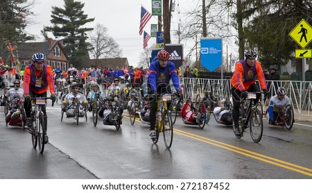 HOPKINTON, USA - APRIL 20: Athletes with disabilities heading fast to Boston downtown during the Boston Marathon 2015 a few seconds after the start of the race in Hopkinton, MA, USA on April 20, 2015. - stock photo