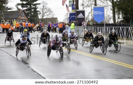 HOPKINTON, USA - APRIL 20: Female athletes with disabilities heading fast from Hopkinton to Boston a few seconds after the start of the Boston Marathon 2015 in Hopkinton, MA, USA on April 20, 2015.  - stock photo
