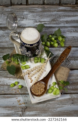 Hops and malt seeds and spikes traditional beer jug on cloth napkin - stock photo