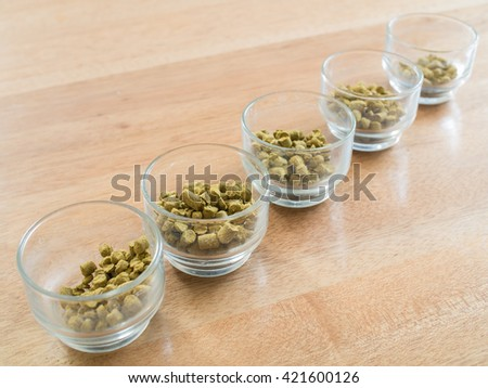 Hops pellets in glass cupsl for brewing beer - Beer ingredient - stock photo
