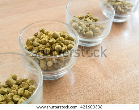 Hops pellets in glass cupsl for brewing beer - Beer ingredient ( Space and composition for text ) - stock photo