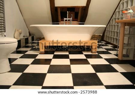 horizonal view of bathtub on black and white tile floor - stock photo
