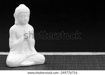 Horizontal black and white shot of a white figure in meditation pose - stock photo