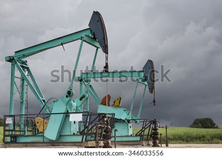 horizontal close up image of two green oil wells sitting under a dark stormy grey sky in the summer time.