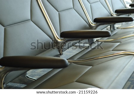 Horizontal close-up of a row of empty seats at airport terminal