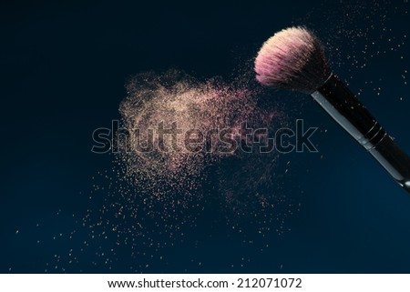 Horizontal close-up photo of professional   black make-up brush with pink powder in motion isolated on blue background with copy place - stock photo
