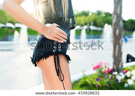 Horizontal close-up picture of a body of attractive girl standing in park. She wears short black shorts, T-shirt. She holds her hand on hip. - stock photo