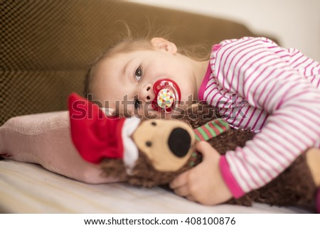 horizontal close up portrait of a little girl wearing her pink pajamas and pacifier laying with her head on a pillow and hugging a brown fluffy teddy bear with Santa hat  - stock photo