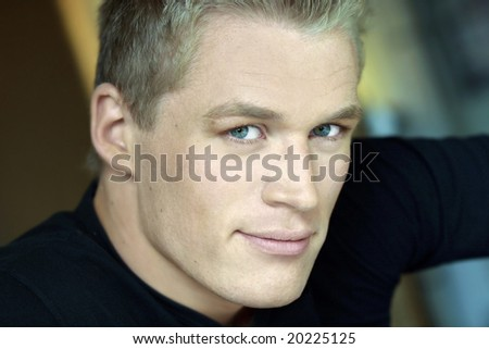 Horizontal close-up portrait of young male model with blond hair and green eyes - stock photo