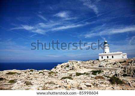 Horizontal color image of a white lighthouse in the distance. Rocks and plants in the bottom part of the image and a beautiful blue sky on top.