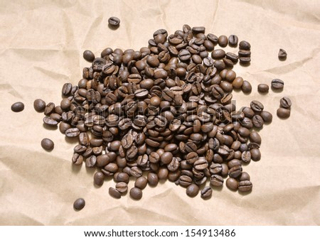Horizontal composition with coffee grains lying on brown paper