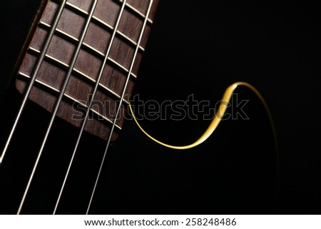 Horizontal detail of the fret board of a bass guitar, on a dark background. - stock photo