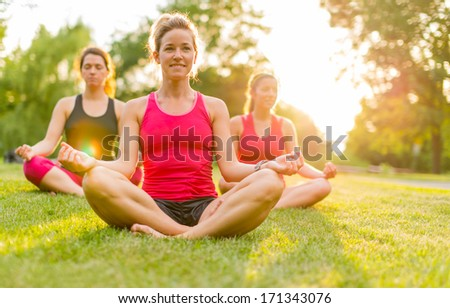 horizontal detail of women doing yoga outdoors at sunset with lens flare. Defocused - stock photo