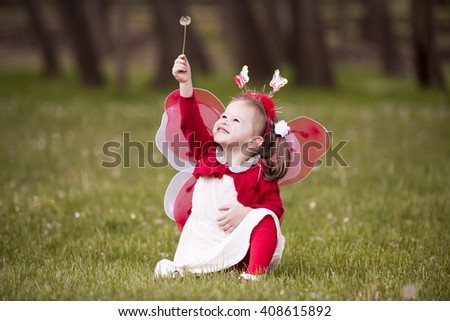horizontal full length portrait of a little girl dressed in a white dress red blouse red stockings wearing butterfly wings on her back and butterfly hairband,holding a dandelion in the park in spring - stock photo