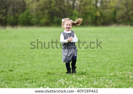 horizontal full length portrait of a little girl walking carefree in a field of green grass and dandelions, carrying a bottle of water, smiling with her mouth open with background forest in spring - stock photo