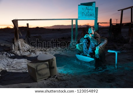 Horizontal image of a Asia-American man in his 30s watching television in desert ruins. - stock photo