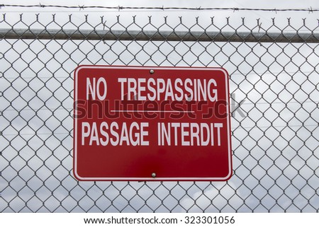 horizontal image of a big red sign saying No Trespassing in english and french language posted on a chain link wire fence with a cloudy sky in background with copy space. - stock photo