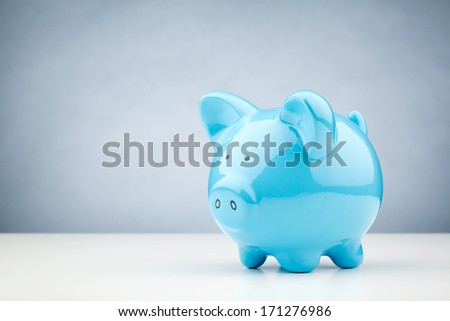 Horizontal image of a blue piggy bank standing on a white desk surface with copy space on the background. - stock photo