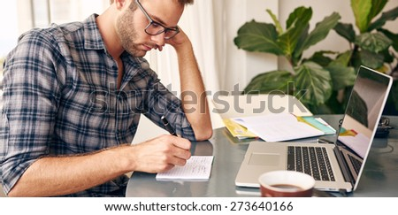 Horizontal image of a businessman writing notes on a writing pad while sitting at his desk behind his new notebook with his morning coffee - stock photo