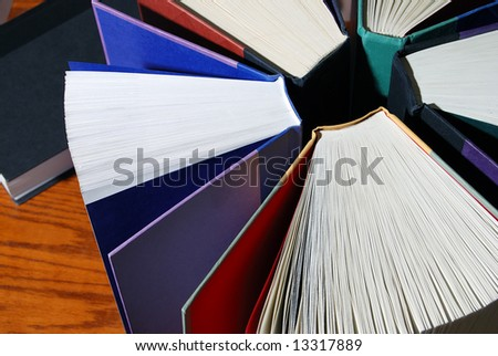 Horizontal image of a group of colorful books standing upright in a circle against a wooden desk.  One book is lying on its side in the background. - stock photo
