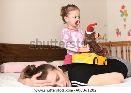 horizontal image of a little girl playing with a yellow toy car and a fluffy brown teddy bear with Santa hat on the bedroom bed in her pajamas and pacifier in her mouth while her mother is sleeping - stock photo