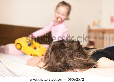 horizontal image of a little girl playing with a yellow toy car on the bedroom bed in her pajamas and pacifier in her mouth while her mother sleeps - stock photo