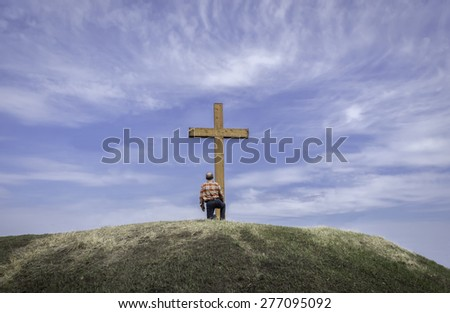 horizontal image of a man kneeling by a wooden cross on a grassy hill surrounded by a beautiful blue sky with wispy white clouds floating by in the summer time. - stock photo