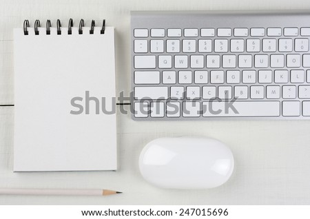 Horizontal image of a white wood home office desk with a computer keyboard, blank note pad, a white pencil, and mouse. A monochromatic still life shot from a high angle. - stock photo
