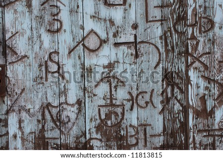 Horizontal image of an old door covered in western branding iron marks - stock photo