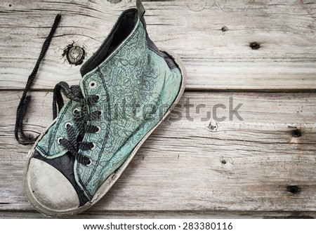 horizontal image of an old worn out faded blue running shoe with black laces on an old wood background with room for text. - stock photo