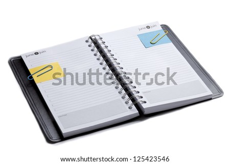 Horizontal image of an open organizer note book with paper clips and post it - stock photo