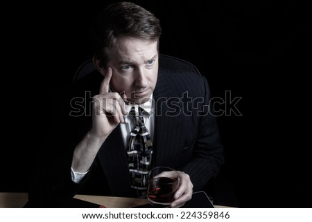 Horizontal image of business man working late with black background  - stock photo