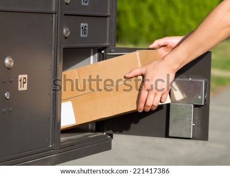 Horizontal image of female hands taking large package out of postal mailbox with green grass and sidewalk in background